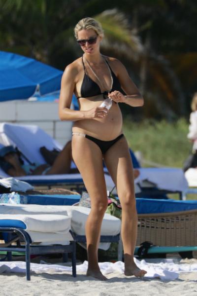 Беременная модель Каролина Куркова гуляет по пляжу в бикини