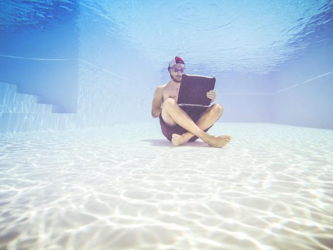 Мужчина, работающий на компьютере под водой