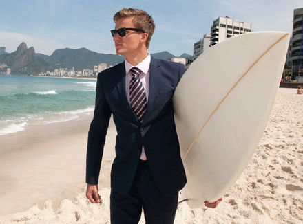 Мужчина в пиджаке с серфом на пляже