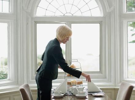 Женщина накрывает на стол