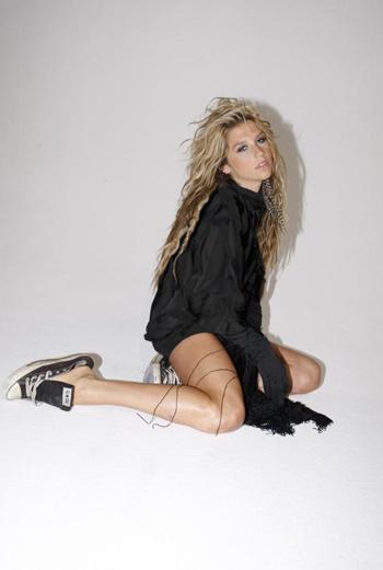 Яркая блондинка носит кеды, широкие рубашки и короткие шорты, при этом выглядит невероятно сексуально благодаря копне шикарных волос и подтянутому телу.
