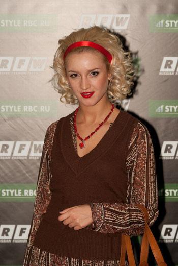 Телеведущая Ольга Бузова появилась и на втором дне RFW. Блуза с восточным орнаментом дополнена жилетом в тон, яркие бусы из камней, атласная лента в волосах и красная помада расставили акценты образа.