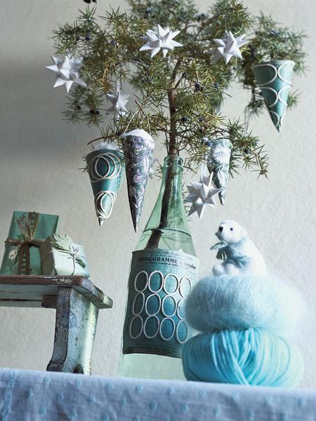 Ветка можжевельника в бутылке превратится в прекрасную рождественскую композицию. Все что для этого нужно — базовые навыки работы с бумагой и чуть-чуть сноровки. Белые плетеные звезды — типично скандинавская традиция. Их дополнят фунтики из упаковочной бумаги. Вата в них символизирует «волосы ангела».