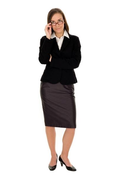 Образ: темно-синяя юбка-карандаш строгого покроя, белая блузка, телесного цвета чулки, классические черные туфли на невысоком каблуке.