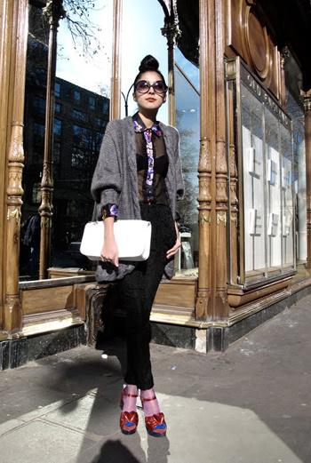 Огромный вязаный кардиган с прозрачной блузкой, узкие брюки, цветные носочки и босоножки, круглые очки и крупный клатч. Эта девушка – наглядная демонстрация одного из самых модных «луков» в Европе.