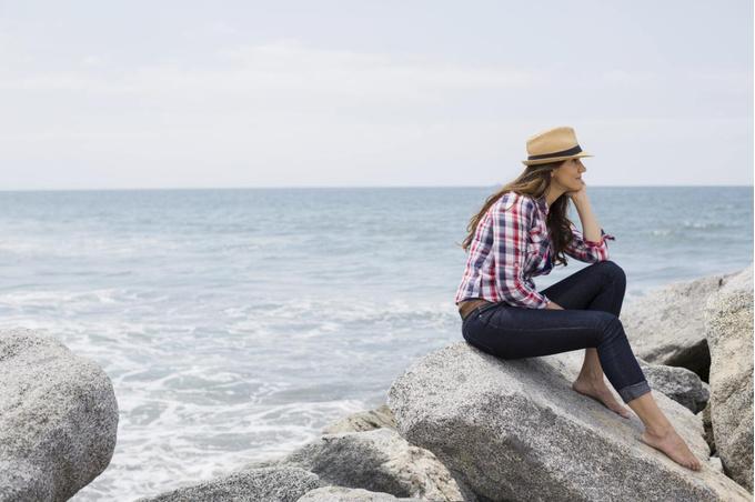 Девушка наслаждается одиночеством на берегу моря