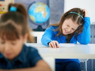 Ребенок сидит за школьной партой