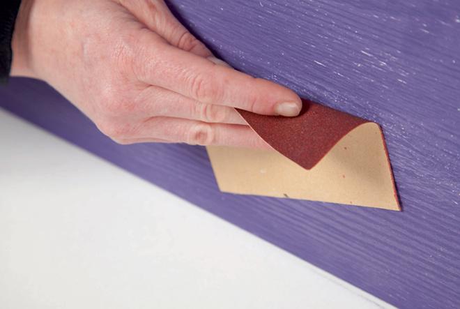 Спустя час-два поверхности, окрашенные в фиолетовый цвет, зачищают наждачной бумагой. Поскольку сосна, изкоторой сделан комод, имеет фактуру, наизделии проявятся белые прожилки.
