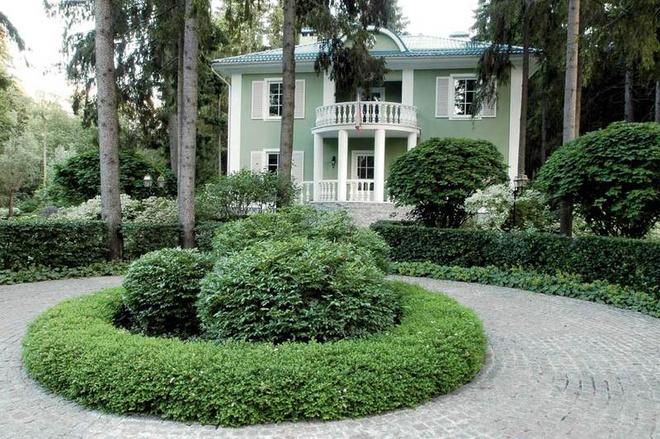 Центральная площадь перед домом обрамлена живой изгородью из боярышника. Шаровидные бересклеты растут в кольце из спиреи японской.