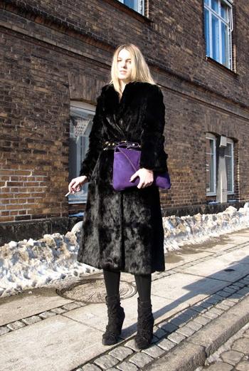 Длинная шуба, полусапожки с выпуклым рисунком и кожаный ремень – жительница столицы Дании разбавила свой строгий образ крупным плоским клатчем насыщенного фиолетового цвета.