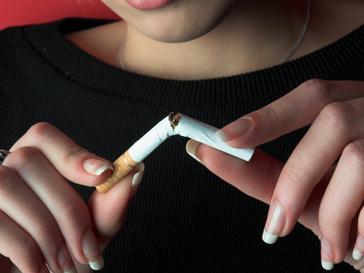 Женщина разламывает сигарету