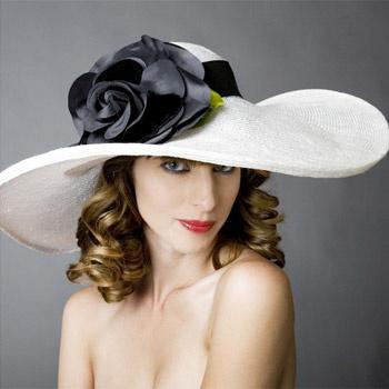 Идеальная модель для торжественной встречи на скачках – широкополая соломенная шляпа. Чуть заметный салатовый лепесток становится изюминкой монохромной цветочной композиции.