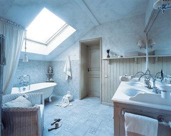 Свет в ванную льется через мансардное окно. Сантехника и смесители от Devon & Devon, подстолье умывальника от Bianchini & Capponi - из салона «Нэксклюзив». Стены вокруг ванны облицованы плиткой, а в менее сырой зоне обшиты деревянными панелями.