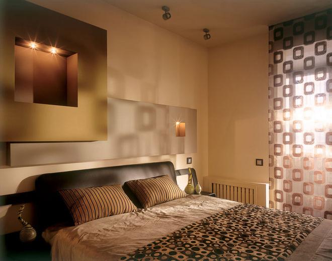 Кровать марки Emme Mobili застелена покрывалом из ткани с оптическим узором от Cravet. Шторы сшиты из ткани от Chivasso.
