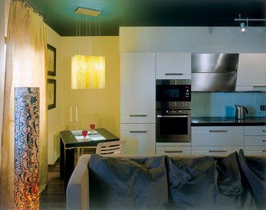 Уголок для завтраков оборудован в нише (она была предусмотрена изначальной планировкой). «Фартук» кухни сделан из матового стекла.