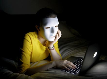 Человек в маске за компьютером