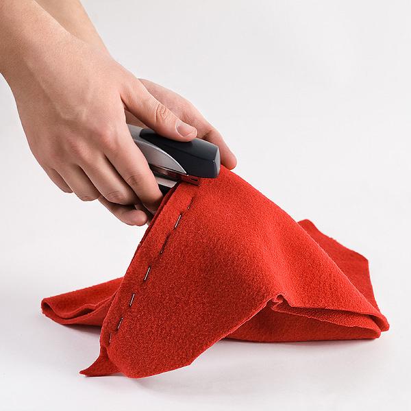Шаг 1. Самый главный элемент нашей композиции – красный колпак. Для того чтобы его сделать, разрежем ткань на два равных куска треугольной формы, а после соединим края степлером. Выворачиваем на лицевую сторону, чтобы не было видно швов от степлера.