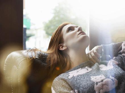 Девушка медитирует, лежа на диване