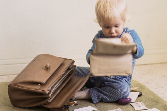 Ребенок рассматривает содержимое маминой сумки