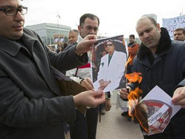 Манифестанты жгут фотографии ненавистного им президента Муаммара Каддафи