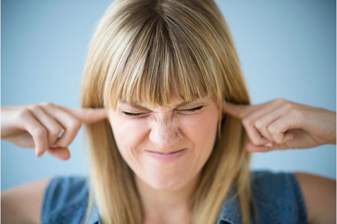 Женщина затыкает уши