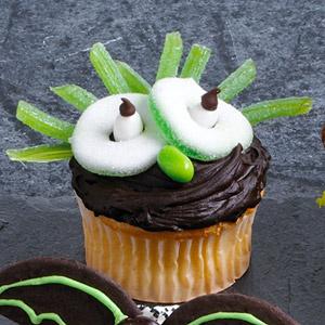 Сова. Для создания образа понадобятся жевательный мармелад, семечки в глазури или мятные драже и шоколадная паста, которой обмазывается кекс.