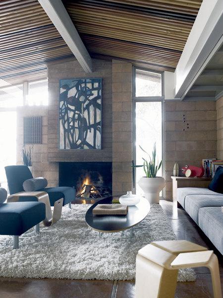 Центральное место в гостиной занимает столик Elliptical Table от Чарльза и Рэй Имс. Подставка для журналов из гнутой фанеры спроектирована хозяином дома, а абстрактная живопись над камином - работа его жены Мелиссы.