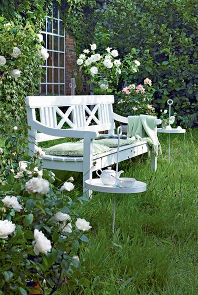 Согласитесь, найти лучшее место для чтения и разговоров, чем садовая скамейка, сложно. Для большего комфорта на ее сиденье можно положить подушки, а справа и слева поместить (точнее, воткнуть в землю) пару столиков. Ножки им заменяет стержень с петлей наверху, а потому столики несложно перенести на другое место.