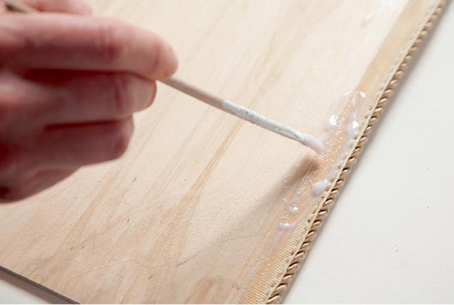 По периметру фанерного листа (он нужен, чтобы закрыть сзади скрепки, удерживающие искусственную кожу наДСП) клеем длядекупажа фиксируют тесьму.