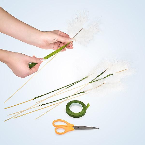 Используя тейп-ленту, прикрепляем кусочки перьев к белым палочкам. Обратите внимание: каждый следующий виток обмотки должен чуть-чуть перекрывать предыдущий, а перьевые волокна должны быть направлены только вверх.