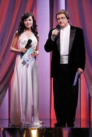 Ведущие шоу одеты соответственно: Анастасия - в белом платье в пол, Дмитрий - в черном фраке.