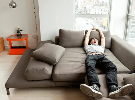 Подросток зевает на диване