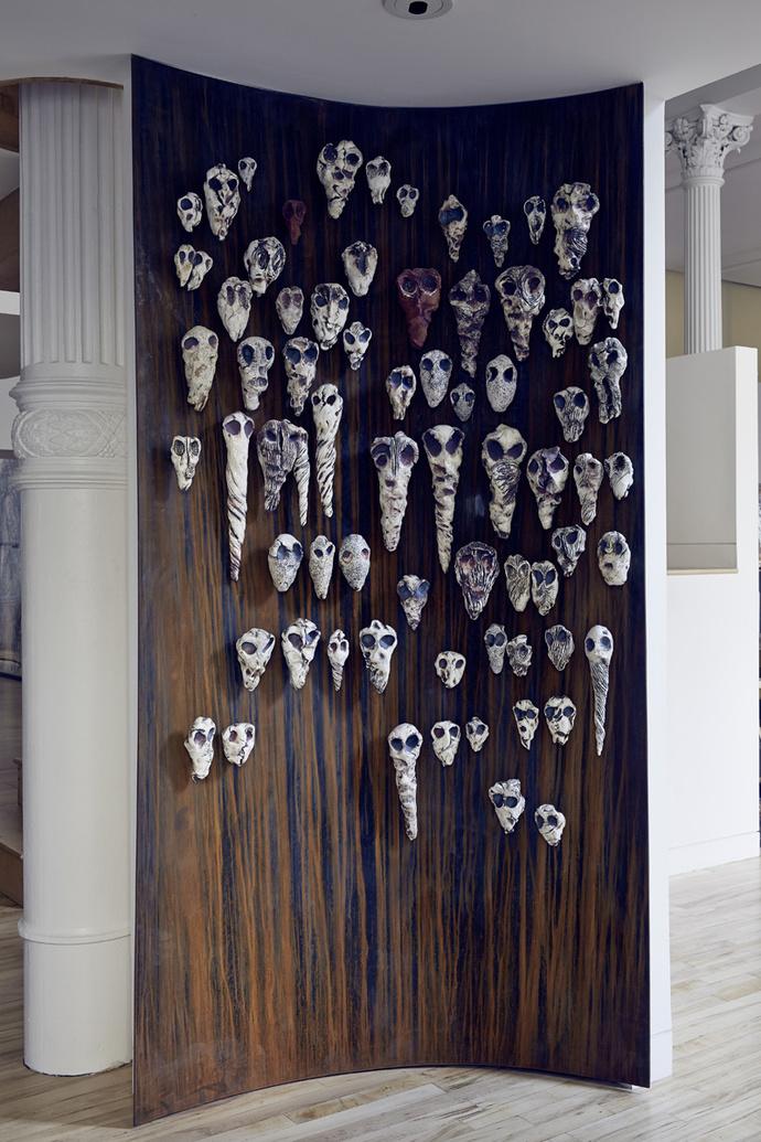 Холл. Стену с отделкой из листов ржавого металла украшают работы Мишель Оки Донер из серии Soul-Catchers, фарфор, металл, 2010 год.
