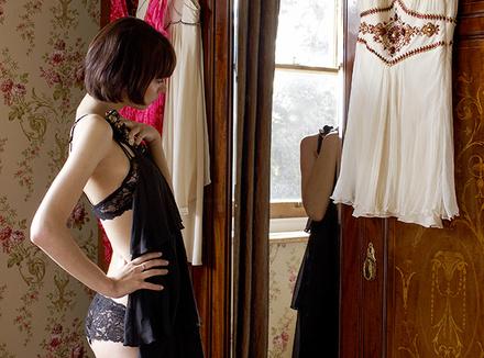 Женщина примеряет платье