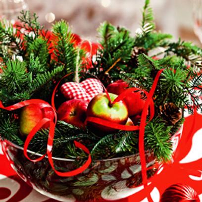 Вместе с яблоками или другими зимними фруктами в прозрачную вазу можно положить пушистый еловый лапник, несколько елочных игрушек и ленту серпантина.