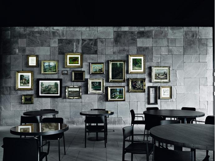 «Картинная галерея» в ресторане отеля — яркий пример виртуозной игры Пьеро Лиссони со стилями и традицией. Картины в классических позолоченных рамах эффектно смотрятся на фоне стены из серого камня. Кресла, Porro.