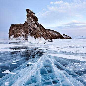 Исключительная прозрачность льда позволяет вблизи берега видеть дно и заглянуть в чернеющие глубины Байкала.
