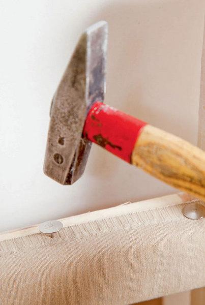 Используя декоративные гвозди и молоток, на створках закрепляют полотна с карманами, подгибая края. С тыльной стороны створок аналогичным способом фиксируют полотна без карманов.