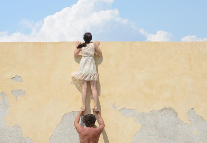 Женщина заглядывает за высокую стену