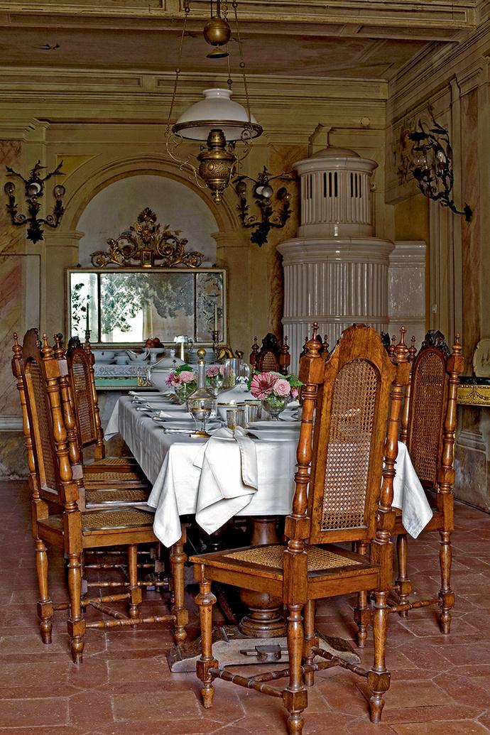 Столовая на первом этаже. На заднем плане — зеркало XVIII века. Массивная керамическая печь сделана в 1950 году в Австрии по эскизу деда хозяина — знаменитого археолога и историка Рануччио Бьянки Бандинелли.