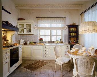 Кухня с филенчатыми дверцами куплена в салоне «Танго». Обеденный стол и стулья от Saldo. Ностальгический абажур с бахромой (давняя мечта хозяев дома) сделан по эскизам Ирены Барене.