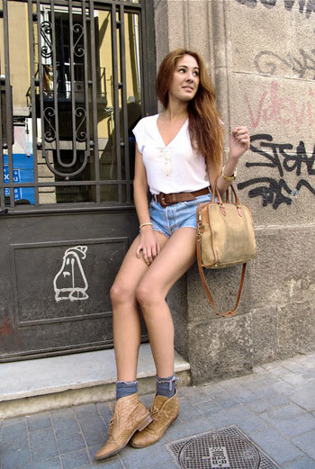 Короткие джинсовые шорты вместе с белой блузкой или майкой – идеальный комплект для прогулок по парку или похода за покупками. Жительница Мадрида дополняет образ грубыми ботинками и аксессуарами.