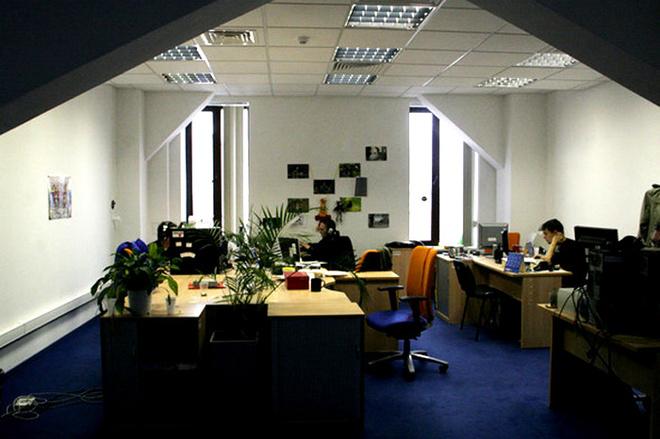 Большие окна, цветы, картинки на стенах, творческий беспорядок – рабочая зона выглядит обычно.
