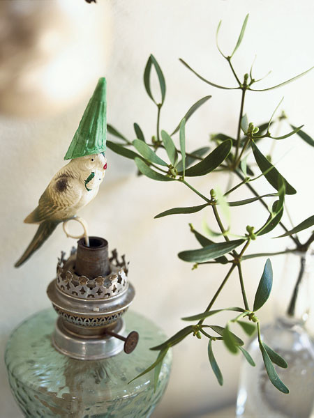 Лавр, испокон веков символизирующий мир, справится с ролью новогоднего дерева не хуже традиционной ели. Достаточно украсить его стеклянными шарами. На старинной керосиновой лампе (вернисаж в Измайлове) — стеклянный попугай в колпачке, сделанном из рожка для мороженого.