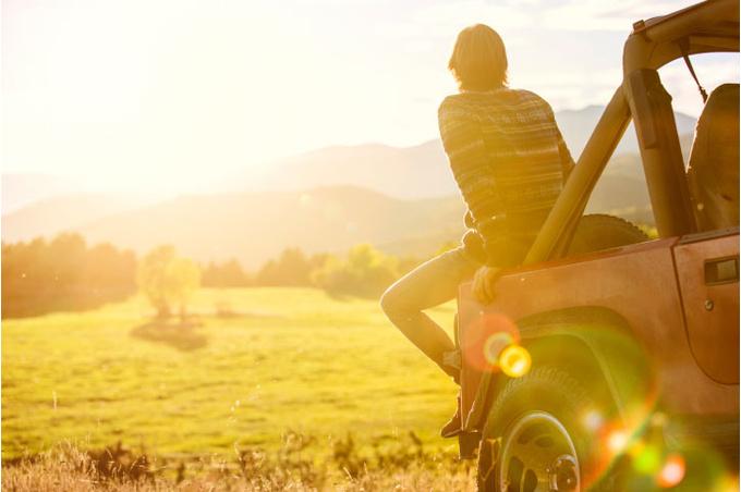Молодой мужчина сидит на капоте машины