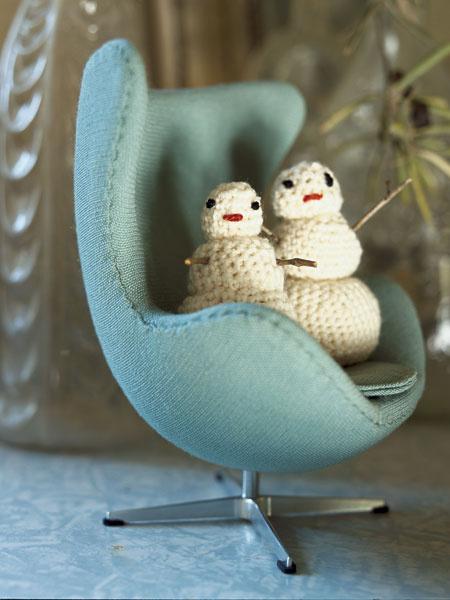 В миниатюрной копии кресла Egg Арне Якобсена устроились два снеговика, связанные крючком. Вы легко сделаете таких же. Особенно, если воспользуетесь книгой Ф. Мак-Таг «Вязаные игрушки».