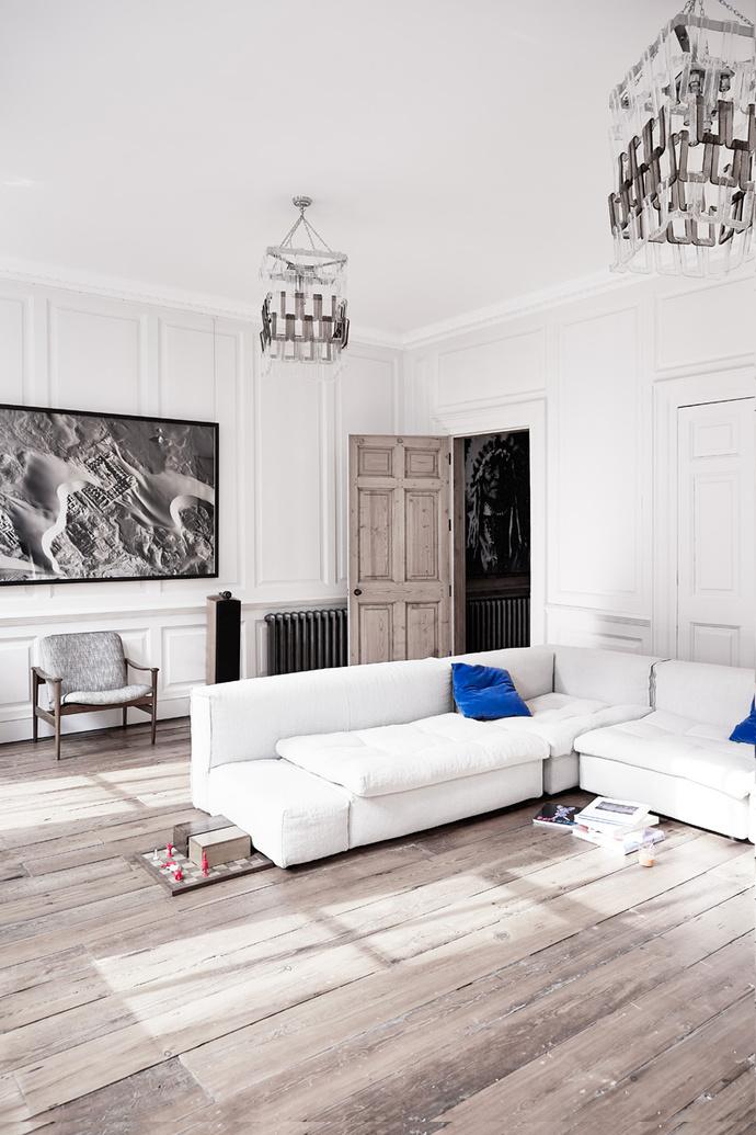 Гостиная. На потолке — винтажные люстры 70-х годов XX века. Белый раскладной диван Nap от Arflex.