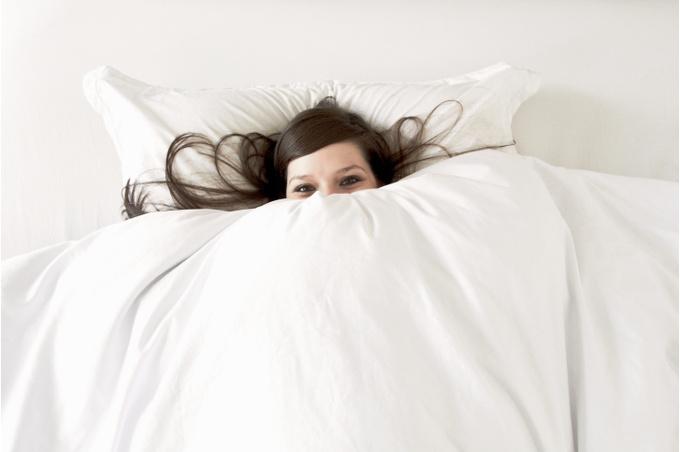 Девушка в игривом настроении под одеялом