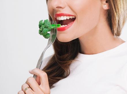 Женщина ест брокколи