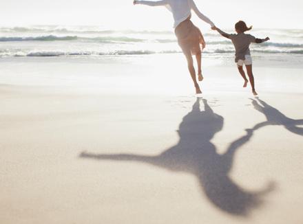 Мама с ребенком бегут по пляжу